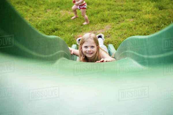 Portrait of happy girl sliding while brother playing in playground Royalty-free stock photo