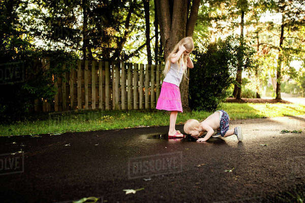 Girl looking at brother licking puddle on road Royalty-free stock photo