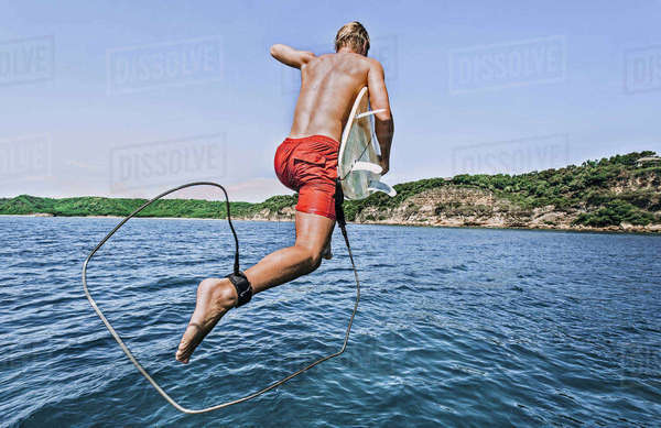Shirtless man with surfboard jumping into sea against sky during sunny day Royalty-free stock photo