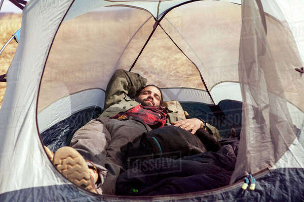 Full length of man sleeping in tent with dog at campsite Royalty-free stock photo
