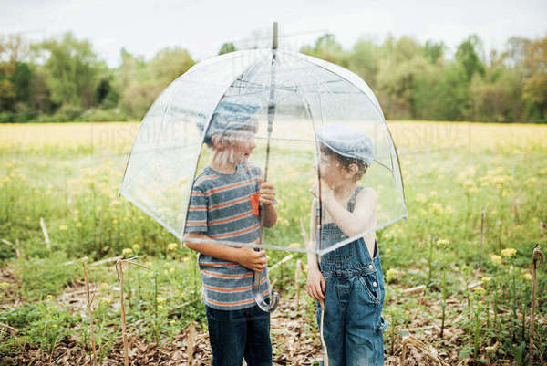 Boys talking while standing under umbrella on field Royalty-free stock photo