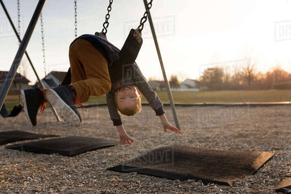 Portrait of happy boy leaning upside down on swing at playground Royalty-free stock photo