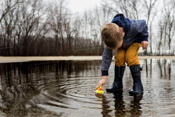 Boy playing with rubber duck in puddle Royalty-free stock photo