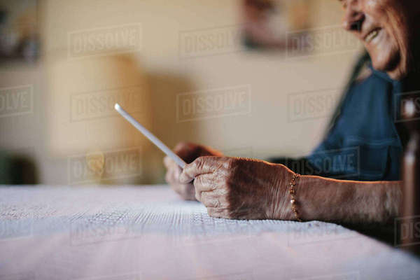 Cropped image of senior man holding tablet computer at table Royalty-free stock photo