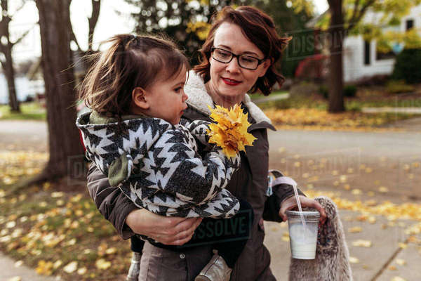 Mother carrying daughter while holding disposable glass at park Royalty-free stock photo