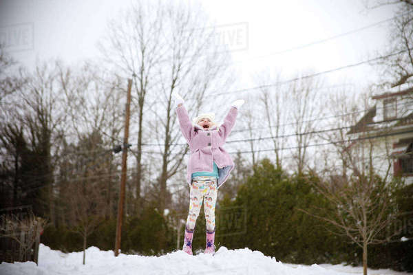 Cheerful girl with arms raised jumping on snow against sky Royalty-free stock photo