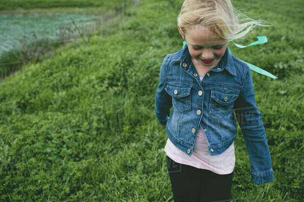 Girl smiling while walking on grassy field Royalty-free stock photo