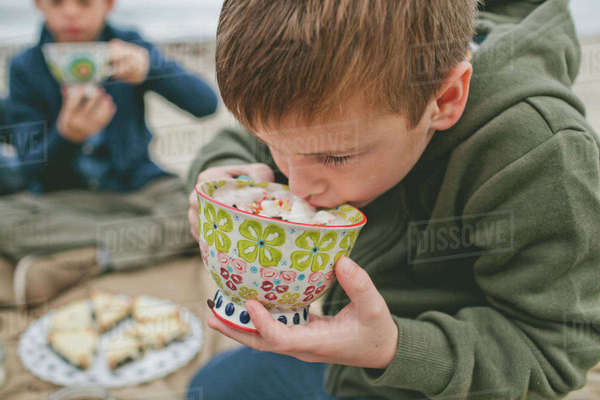 Boy drinking from cup while sitting at beach with brother in background Royalty-free stock photo