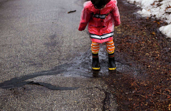 Boy playing in puddle on street Royalty-free stock photo