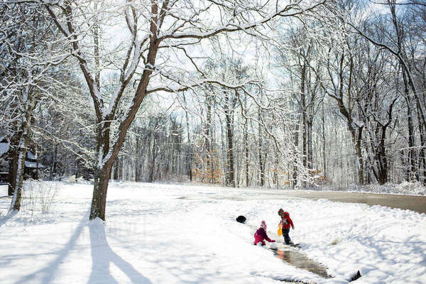 Siblings playing on snow covered field Royalty-free stock photo
