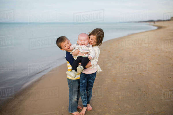 Siblings enjoying at beach against cloudy sky Royalty-free stock photo