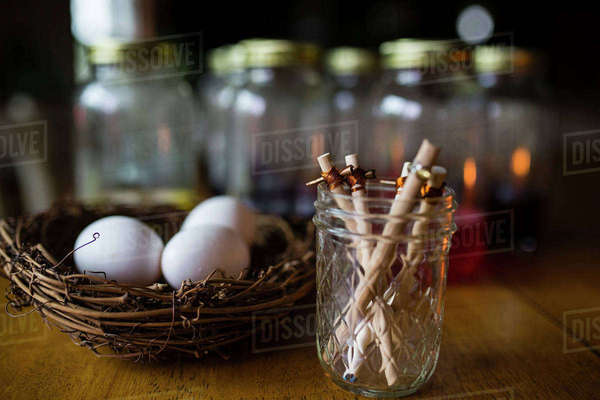 Sticks in jar by eggs on wooden table Royalty-free stock photo