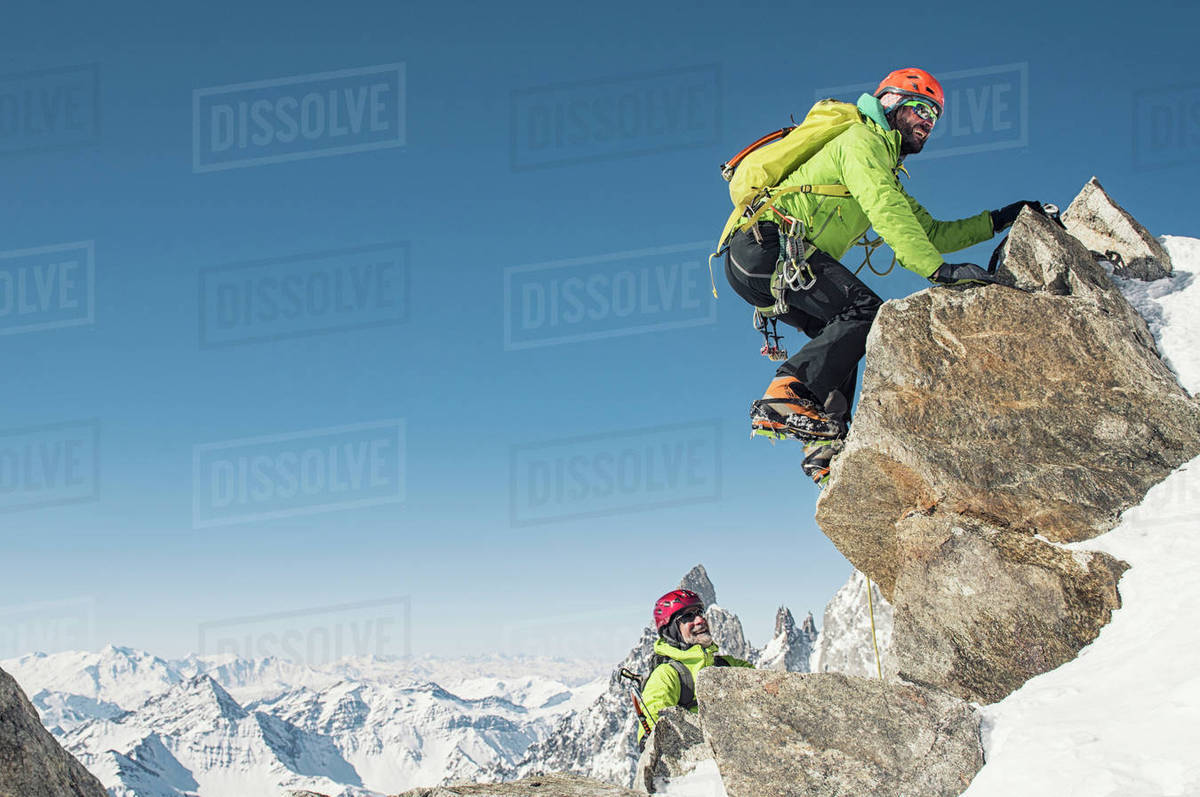 Hikers climbing mountain against clear blue sky during winter on sunny day Royalty-free stock photo