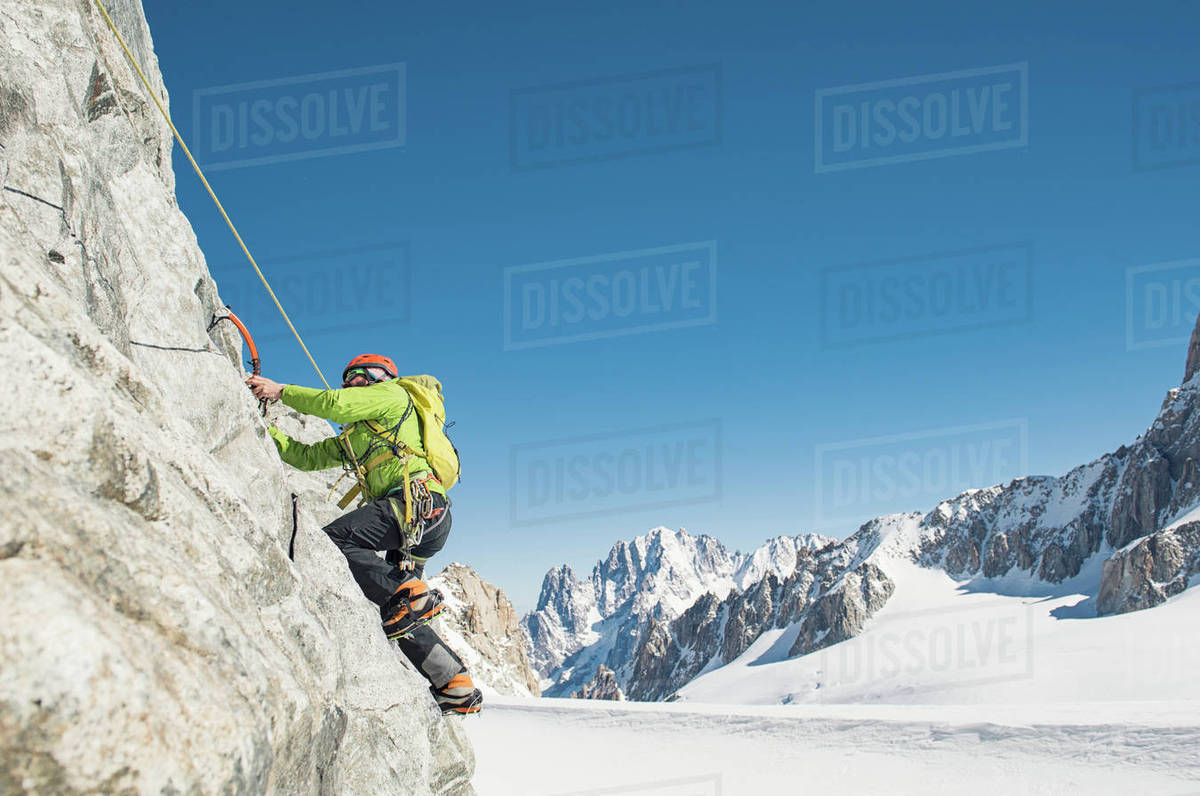 Side view of hiker climbing mountain against clear blue sky during winter Royalty-free stock photo