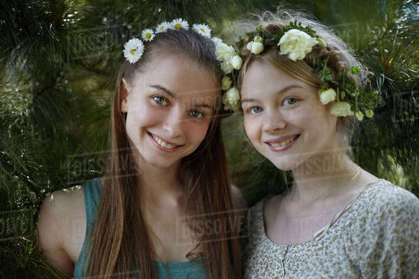 Portrait of happy friends wearing tiaras while standing by plants at park Royalty-free stock photo