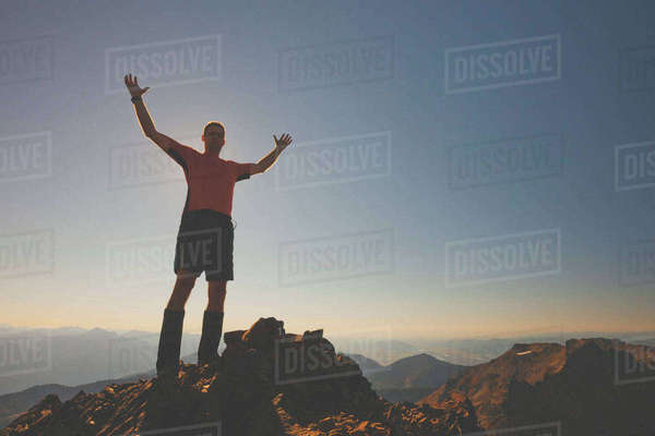 Low angle view of man standing on mountain with arms raised against clear sky during sunset Royalty-free stock photo