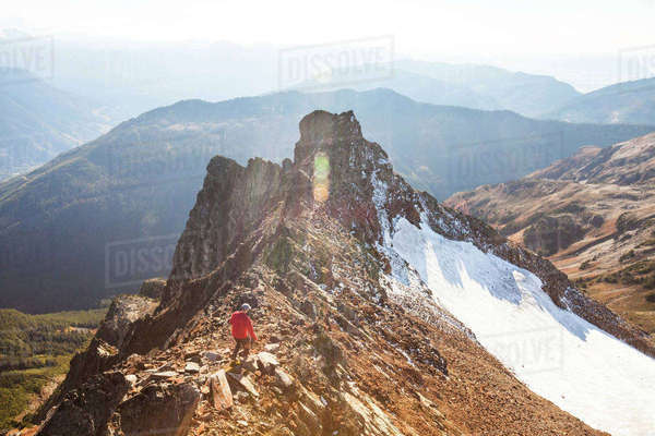 High angle view of male hiker walking on rocky mountains against sky during sunny day Royalty-free stock photo