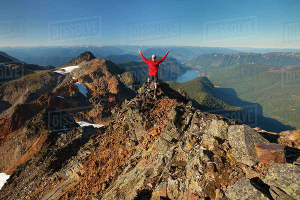 Rear view of male hiker with arms raised looking at view while standing on rocky mountains Royalty-free stock photo