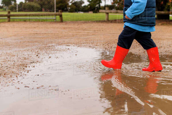 Low section of boy walking in puddle at playground Royalty-free stock photo