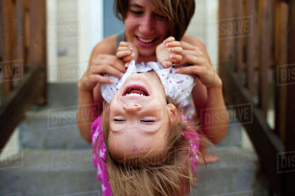 Happy mother playing with daughter while sitting on steps Royalty-free stock photo
