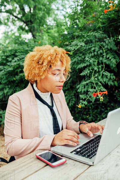 Woman using laptop computer while sitting at park Royalty-free stock photo