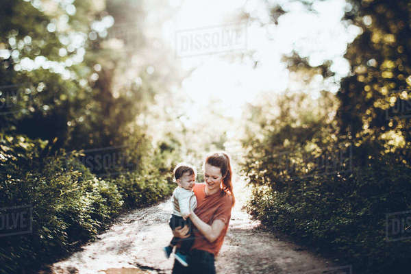 Mother carrying son while standing on dirt road at forest Royalty-free stock photo