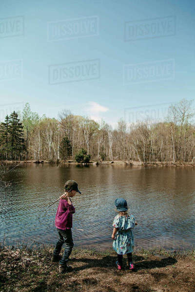 Siblings playing while standing at lakeshore against sky Royalty-free stock photo