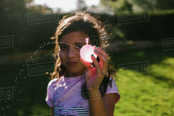 Portrait of girl spraying from water bomb at backyard Royalty-free stock photo