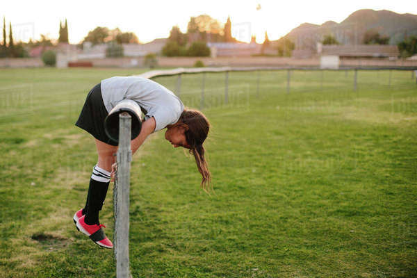 Full length side view of girl leaning over fence at playground Royalty-free stock photo