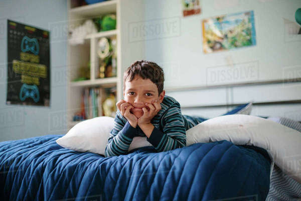 Portrait of boy lying on bed at home Royalty-free stock photo