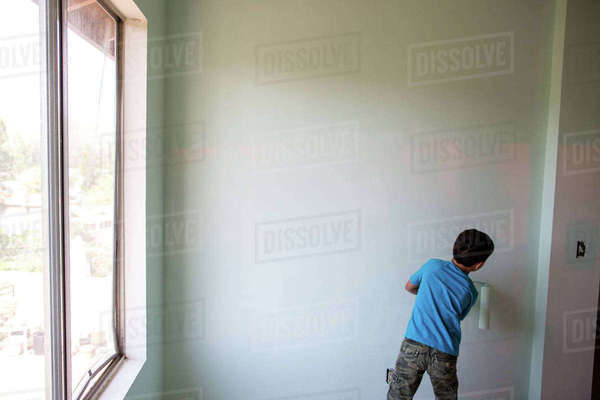 Rear view of boy painting wall with paint roller at home Royalty-free stock photo
