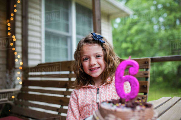 Portrait of happy girl sitting by birthday cake with number 6 candle at porch Royalty-free stock photo