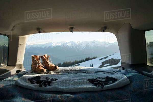 Hiking boots and blanket in sports utility vehicle with snowcapped mountains in background Royalty-free stock photo