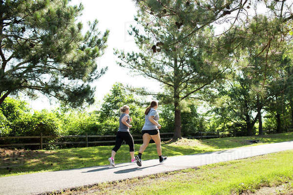 Full length of mother and daughter jogging on footpath at park during sunny day Royalty-free stock photo