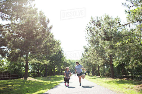 Mother and daughter stretching legs while exercising on footpath at park during sunny day Royalty-free stock photo
