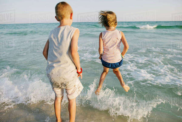 Rear view of siblings playing with waves at beach Royalty-free stock photo