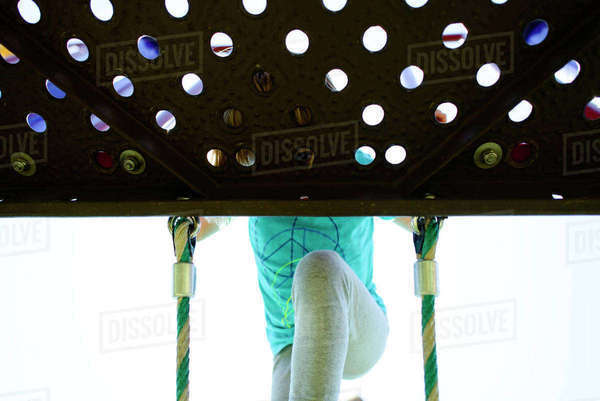 Low angle view of girl peeking through hole while climbing rope ladder at playground Royalty-free stock photo