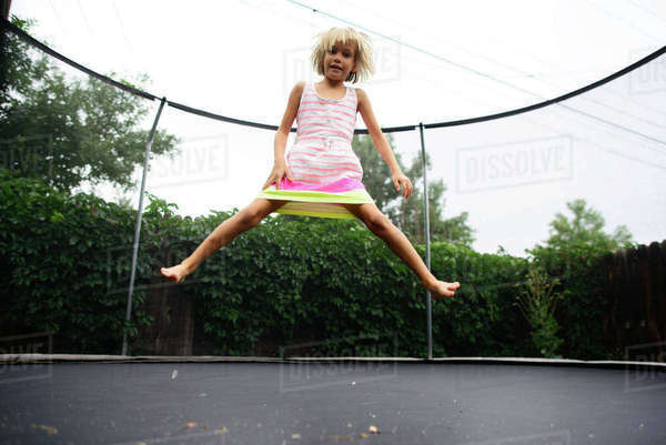 Low angle portrait of girl jumping on trampoline at park against clear sky Royalty-free stock photo