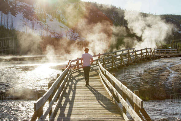 Rear view of hiker walking on boardwalk by hot springs at Yellowstone National Park Royalty-free stock photo