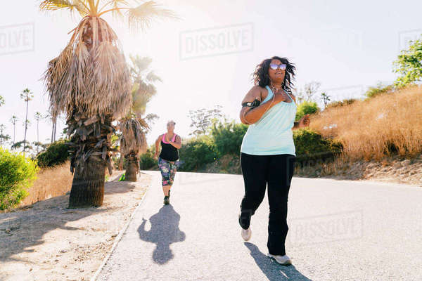 Female friends jogging on street against clear sky during sunny day Royalty-free stock photo