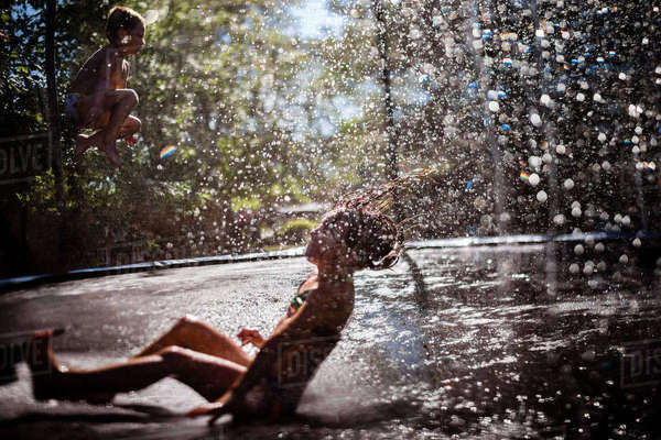 Playful siblings playing on wet trampoline at playground Royalty-free stock photo