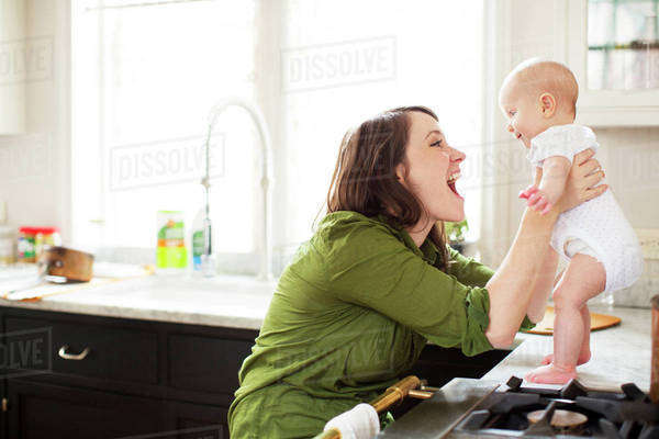Mother playing with her baby son (2-5 months) in kitchen Royalty-free stock photo