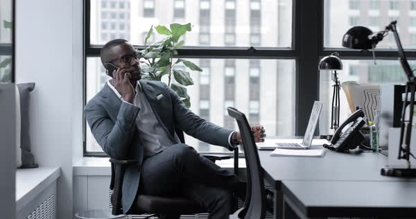 Lockdown shot of businessman answering smart phone while sitting at desk in office Royalty-free stock video