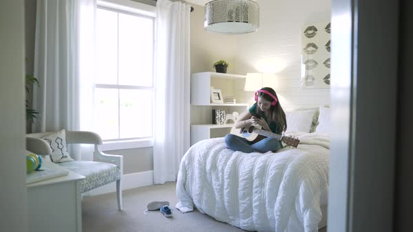 Handheld shot of happy teenage girl using smart phone while sitting with guitar on bed Royalty-free stock video