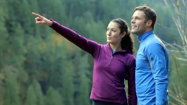 Handheld shot of happy sporty couple talking in forest Royalty-free stock video