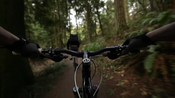 POV lockdown shot of mountain bikers riding bicycle on footpath at forest Royalty-free stock video