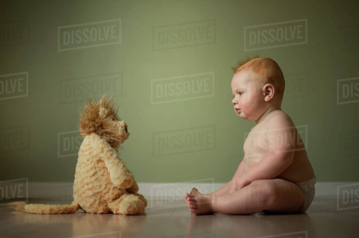 Shirtless Baby Boy Looking At Stuffed Toy While Sitting On Floor