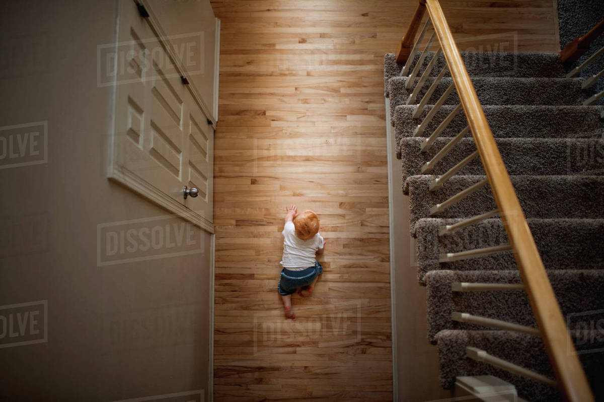 Overhead view of baby boy crawling on hardwood floor at for Hardwood floors and babies