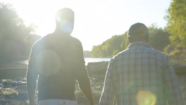 Handheld shot of father and son talking while walking on lakeshore during sunny day Royalty-free stock video