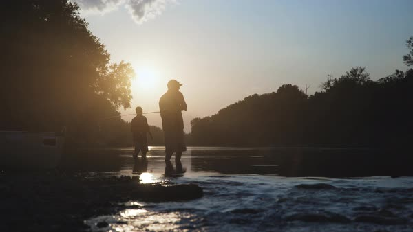 Dolly shot of silhouette men fishing in lake against sky during sunset Royalty-free stock video